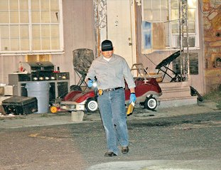 The Sentinel-Record/Grace Brown CRIME SCENE: Hot Springs police Detective Nathan Rines investigates the scene of a shooting that occurred late Thursday in the 600 block of Albert Pike. A Hot Springs woman, 55, was reportedly shot in the back by an unknown assailant firing from a vehicle.