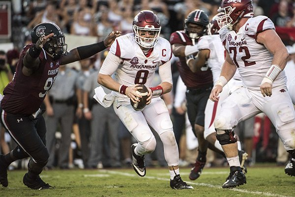 Arkansas quarterback Austin Allen (8) attempts to escape pressure from South Carolina defensive lineman Dante Sawyer, left, during the second half of an NCAA college football game Saturday, Oct. 7, 2017, in Columbia, S.C. (AP Photo/Sean Rayford)