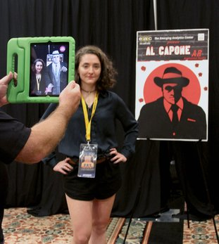 The Sentinel-Record/Grace Brown Loki Rasmussen helps demonstrate the Al Capone Virtual Selfie application brought to the Hot Springs Documentary Film Festival by the Emerging Analytics Center at the University of Arkansas at Little Rock. The application, that was featured the first weekend of the festival, allowed guests to take a virtual selfie with the mobster using augmented reality.