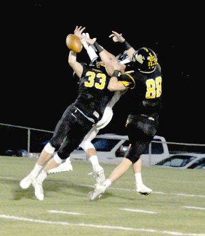 MARK HUMPHREY ENTERPRISE-LEADER Twin brothers Stone Bryant (No. 33) and Collin Bryant (No. 88) combine to break up a pass inside the Tiger five. Both brothers had interceptions and the Tigers forced Shiloh Christian to turn the ball over on downs five times in the first half. Prairie Grove won 35-21 Friday.