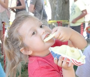 LYNN KUTTER ENTERPRISE-LEADER Abbi Lee, 4, of Farmington, enjoys a fresh slice of apple at the Arkansas Apple Festival in Lincoln. Volunteers under the red and white striped tent at the festival stayed busy peeling, slicing and handing out baskets of free apple slices to visitors.