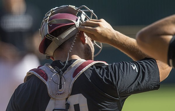 An earpiece is shown on Arkansas catcher Zack Plunkett during a fall scrimmage at Baum Stadium in Fayetteville.
