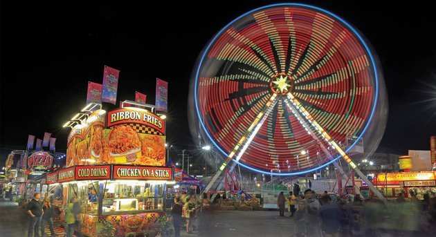 visitors-to-the-arkansas-state-fair-walk-the-midway-thursday-night-as-rides-and-food-booths-light-up-the-night-sky