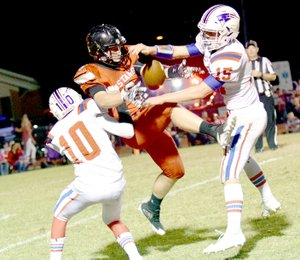Photo by Rick Peck McDonald County's Oakley Roessler makes a circus catch between East Newton defensive backs Austin Brewster (10) and Brett Pendergraft (15) during the Mustangs' 54-0 win on Oct. 6 at MCHS.