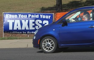 The Sentinel-Record/Richard Rasmussen TIME TO PAY: A motorist passes a sign near the intersection of Lakeshore Drive and Higdon Ferry Road on Wednesday reminding residents that their real and personal property taxes are due Monday.