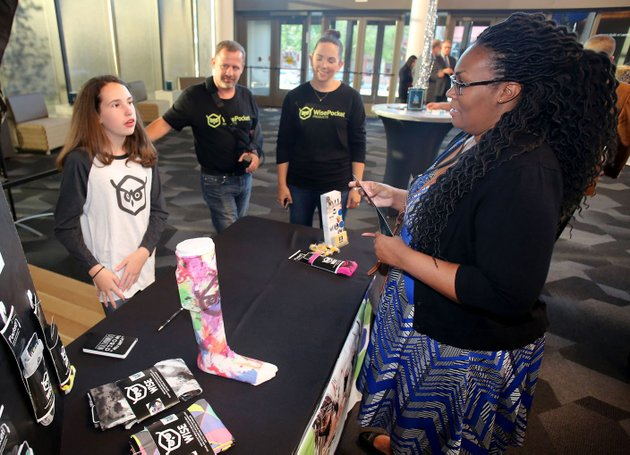nwa-democrat-gazettedavid-gottschalk-sofi-overton-from-left-12-with-wise-pocket-products-stands-with-her-parents-john-and-brandy-overton-thursday-as-she-describes-her-socks-and-leggings-with-pockets-to-tamica-stubblefield-with-cox-business-during-the-get-started-nw-arkansas-event-at-the-walton-arts-center-in-fayetteville-overton-is-one-of-five-local-startups-that-gave-a-quick-pitch-for-their-business-in-front-of-a-panel-of-judges-each-trying-to-win-11500-in-money-and-support