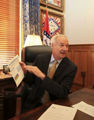 Gov. Asa Hutchinson talks Tuesday in his office about how President Donald Trump's decision to end a subsidy for insurance companies will affect Arkansas Works.
