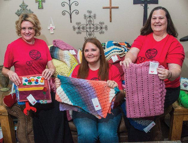 kim-jasmin-from-left-rena-edwards-and-alisa-branigan-members-of-cabot-crafters-for-a-cause-hold-up-some-of-their-creations-the-group-meets-once-a-month-and-regularly-donates-handmade-goods-to-people-in-need