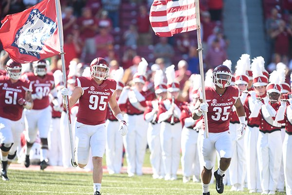 Arkansas defensive lineman Jake Hall (95) and linebacker Dwayne Eugene (35) carry flags onto the field prior to a game against New Mexico State on Saturday, Sept. 30, 2017, in Fayetteville.