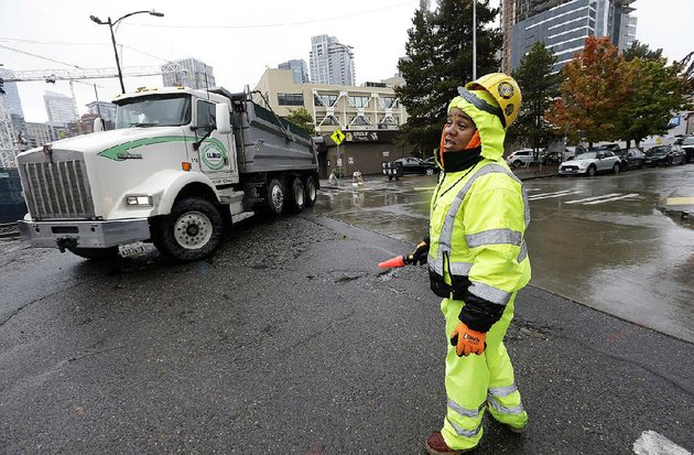 a-construction-worker-directs-traffic-around-a-construction-site-near-amazons-headquarters-on-tuesday-in-seattle-today-is-the-deadline-for-cities-to-submit-bids-for-amazons-second-headquarters-development