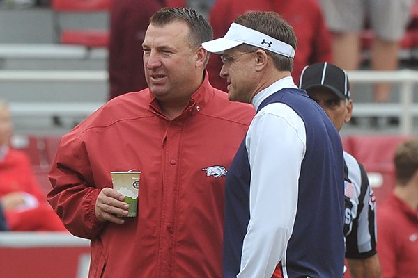Arkansas coach Bret Bielema, left, talks with Auburn coach Gus Malzahn prior to a game Saturday, Oct. 24, 2015, in Fayetteville.