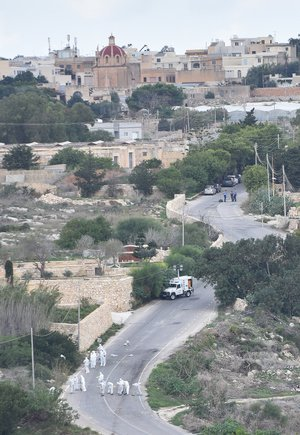 Forensic police work on the main road in Bidnija, Malta, which leads to Daphne Caruana Galizias house, looking for evidence on the blast that killed the journalist as she was leaving her home, Thursday, Oct. 19, 2017.