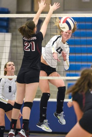 Bentonville High's Grayce Joyce (23) spikes the ball past Springdale High's Graycie Bohannan on Wednesday during the Class 7A state volleyball tournament in Conway.