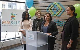 The Associated Press HEALTH CARE: Allison O'Toole, second from right, speaks to the media at the new offices of Briva Health, MNsure's largest enrollment partner, in Minneapolis. Health care consumers in most of the country are encountering a world of confusion and chaos as the open enrollment period to sign up for coverage approaches. The outlook is decidedly different in the 12 states that operate their own marketplaces. California, Colorado, Minnesota and other states that operate autonomous exchanges are pulling out all the stops to inform consumers. Also shown, from left, Hodan Guled, chief executive officer of Briva Health, Minneapolis Major Betsy Hodges and at right, Emily Piper, commissioner of Minnesota Human Services.
