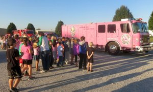 Photo by Susan Holland Students, teachers and staff poured out onto the parking lot at Gravette Upper Elementary School early on Monday morning, Oct. 9, to greet Pink Heals tour members. The youngsters were fascinated by the big pink fire truck, pink ambulance and police car and were excited to be able to help honor their schoolmates, Brooklyn Carte and Sarah Hollingworth, fifth graders who are battling cancer.