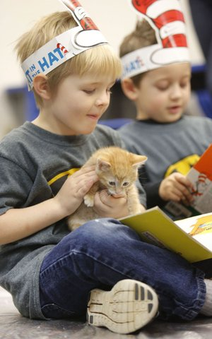 NWA Democrat-Gazette/DAVID GOTTSCHALK Noah Capdeville, a student at T.G. Smith Elementary School in Springdale, reads to an orange tabby fostered by Fabulous Felines of Northwest Arkansas in Springdale. The nonprofit organization readies cats for adoption to permanent indoor homes.