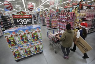 A shopper, left, walks with a store associate in October 2016 in the toy section at Walmart in Teterboro, N.J. As more shoppers shift online, Walmart hopes to make its stores more fun this holiday season. The chain will have parties for customers at its stores for the first time, increase the number of product demonstrations and expand the role of employees who last year helped people find the shortest register lines. Many retailers are trying to make stores more inviting even as they improve online services. (AP Photo/Julio Cortez, File)