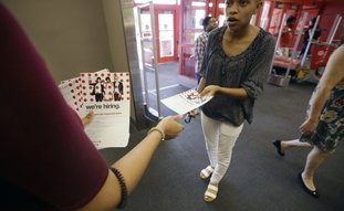 A potential job candidate takes a flyer from a human resources representative Oct. 13 at a Target store in Dallas. The U.S. government issued the October jobs report Friday. (AP Photo/LM Otero)
