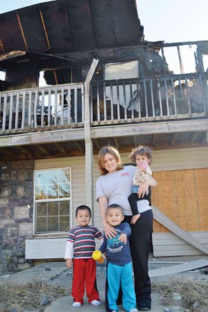 Monica Fortune stands in front of the charred remains of her Queens Manor Apartment unit in 