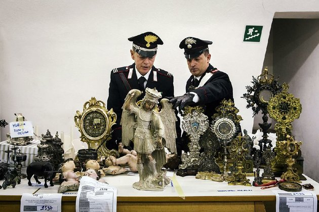 members-of-italys-art-theft-police-unit-examine-a-stolen-16th-century-statue-of-the-archangel-michael-and-other-religious-artifacts-theyve-recovered-after-months-of-investigations-at-their-headquarters-in-naples-italy-the-countrys-60000-churches-are-a-vast-trove-of-artwork-and-artifacts-and-protecting-them-from-theft-is-a-full-time-task