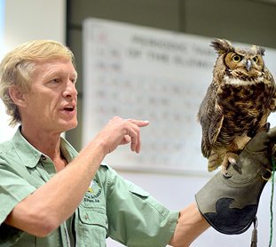 Submitted photo BOGART REHAB: Rodney Paul, owner and director of the Raptor Rehab of Central Arkansas, displayed Bogart the great horned owl Friday during National Park College's First Friday Lecture Series in the Laboratory Science Building. Paul and volunteer Tina Miller were accompanied by five birds from the facility in El Paso in White County.