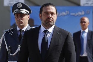 "The Associated Press LEBANON: In this photo taken on Sept. 8, Lebanese Prime Minister Saad Hariri, left, arrives for a mass funeral of ten Lebanese soldiers at the Lebanese Defense Ministry, in Yarzeh near Beirut, Lebanon. Lebanese prime minister Saad Hariri has announced he is resigning in a surprise move following a trip to Saudi Arabia. In a televised address Saturday he slammed Iran and the Lebanese Hezbollah group for meddling in Arab affairs and says ""Iran's arms in the region will be cut off."""
