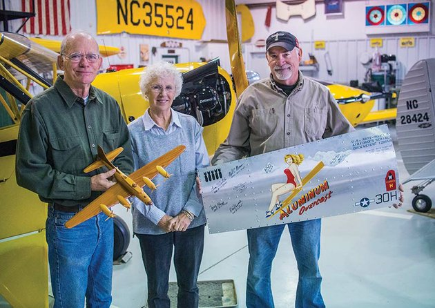 planning-the-upcoming-tour-stop-of-the-world-war-ii-b-17-bomber-at-cantrell-field-in-conway-are-bobby-and-ann-cantrell-from-left-and-bill-hooten-bobby-cantrell-holds-a-model-of-the-plane-while-hooten-shows-an-actual-nose-art-panel-from-the-plane-aluminum-overcast-the-cantrells-both-members-of-the-clinton-chapter-of-the-experimental-aircraft-association-are-co-hosts-for-the-event-and-hooten-is-a-mechanic-with-the-eaas-b-17-touring-program