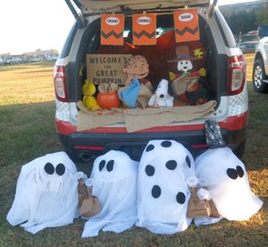 Representatives of Grand Savings Bank joined Charlie Brown, Snoopy and a host of ghostly trick or treaters in welcoming the Great Pumpkin at their trunk at the OCH fall festival Saturday evening, Oct. 28. Bank employees said GSB is expecting to open its new branch in Gravette in about a month.