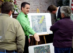 Photo by Randy Moll Gentry's mayor, Kevin Johnston (center), talks to council members Jason Barrett and Janice Arnold about park locations in the city of Gentry and possible uses of those locations for amenities such as baseball diamonds, soccer fields and more at an information gathering meeting in the McKee Community Room at the Gentry Public Library on Oct. 30. Nathan Street of McClelland Consulting Engineers, of Fayetteville, was looking at a map of future park land which was on display.
