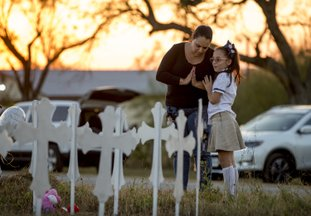 The Associated Press PRAYING IN TEXAS: Meredith Cooper, of San Antonio, Texas, and her 8-year-old daughter, Heather, visit a memorial of 26 metal crosses near First Baptist Church in Sutherland Springs, Texas, on Monday. The gunman of a deadly shooting at the small-town Texas church had a history of domestic violence and sent threatening text messages to his mother-in-law, a member of First Baptist, before the attack, authorities said Monday.