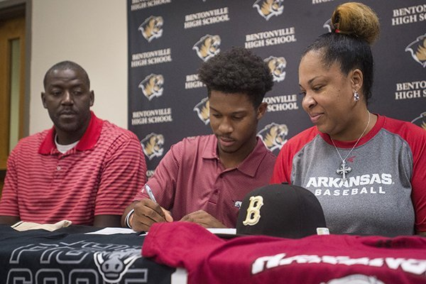 Kam'ron Mays-Hunt, with parents Fess Thompson and Kamra Thompson, signs his national letter of intent to play baseball at Arkansas Wednesday, Nov. 8, 2017, at Bentonville High School's Tiger Athletic Complex.