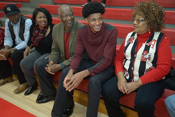 Fort Smith Northside guard Isaiah Joe (center) shares a laugh Wednesday, Nov. 8, 2017, with his grandmother, Emma Watts (from right); grandfather, Lonnie Watts; grandmother Ferry Simmons; and grandfather, Douglas Simmons; before signing to play basketball with Arkansas during a signing ceremony at the school.