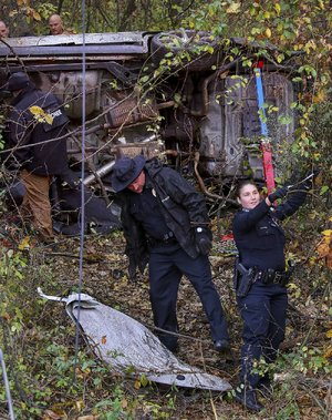 Little Rock police officers investigate a fatal crash Wednesday at 7100 Arch St. in which a speeding car left the roadway and crashed into the woods.