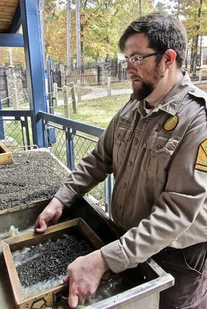 Interpreter Waymon Cox shows Crater of Diamonds State Park visitors how to hunt for the gems by doing wet sifting.
