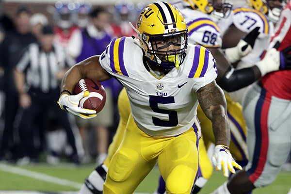 LSU running back Derrius Guice (5) runs for a first down past Mississippi defenders in the first half of an NCAA college football game in Oxford, Miss., Saturday, Oct. 21, 2017. (AP Photo/Rogelio V. Solis)