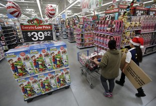 A shopper, left, walks with a store associate in the toy section at Walmart in October 2016 in Teterboro, N.J. Walmart hopes to tempt shoppers with online deals before Black Friday. It's beginning some online deals Thursday and plans to offer most of its Black Friday deals online starting at 12:01 a.m. on Thanksgiving. (AP Photo/Julio Cortez, File)