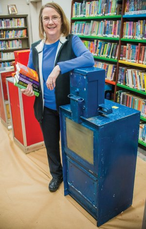 Amy Ketzer, director of the Grant County Library, stands next to a used newspaper stand in the library. The donated stands will be refurbished as Little Free Libraries to be spread across Grant County.