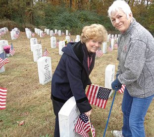Submitted photo VETERANS DAY FLAGS: Baseline-Meridian Chapter USD 1812 President Mary Ellen Laursen, left, and Sheila Beatty, USD 1812 honorary state president, teamed up to help place flags at gravesites in the Arkansas Veterans Cemetery in recognition of Veterans Day.