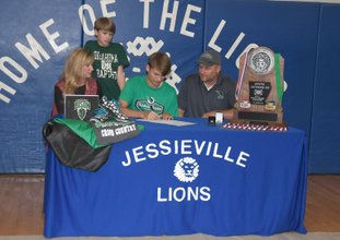 The Sentinel-Record/Mara Kuhn BISON BOUND: Jessieville's Noah Eskew, center, inks his national letter of intent to run cross country and track for Oklahoma Baptist University Friday in the Jessieville Sports Arena. Pictured with the senior are, l-r, his mother Tami Eskew, brother Kaleb Eskew, 11, and father Cory Eskew.