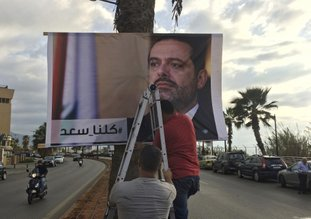 """The Associated Press POSTER: Workers hang a poster of outgoing Prime Minister Saad Hariri with Arabic words that read, """"We are all Saad,"""" on a seaside street Thursday in Beirut, Lebanon. Hezbollah has called on Saudi Arabia to stay out of Lebanese affairs, saying the resignation of Prime Minister Saad Hariri, announced from Riyadh over the weekend, """"has raised many questions."""""""