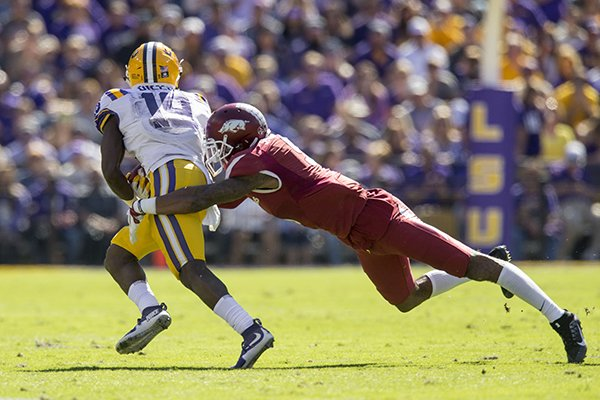 Arkansas safety Santos Ramirez tackles LSU receiver Derrick Dillon during the second quarter of a game Saturday, Nov. 11, 2017, in Baton Rouge, La.