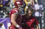 Arkansas offensive lineman Hjalte Froholdt is walked off the field by trainer Matt Summers during a game against LSU on Saturday, Nov. 11, 2017, in Baton Rouge, La.