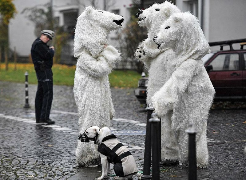 62512f4f20b1 Police keep a close eye Saturday on protesters in polar bear costumes after a  demonstration outside a United Nations climate conference in Bonn