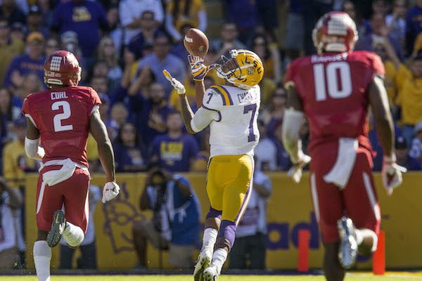 DJ Chark (7), LSU wide receiver, catches a pass as he runs away from Kamren Curl (2), Arkansas cornerback, and Randy Ramsey (10), Arkansas linebacker, for a touchdown in the fourth quarter, Saturday, Nov. 11, 2017 at Tiger Stadium in Baton Rouge, La.