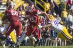 Cole Kelley (15), Arkansas quarterback, evades Rashard Lawrence, LSU defensive end, in the fourth quarter Saturday, Nov. 11, 2017 at Tiger Stadium in Baton Rouge, La.