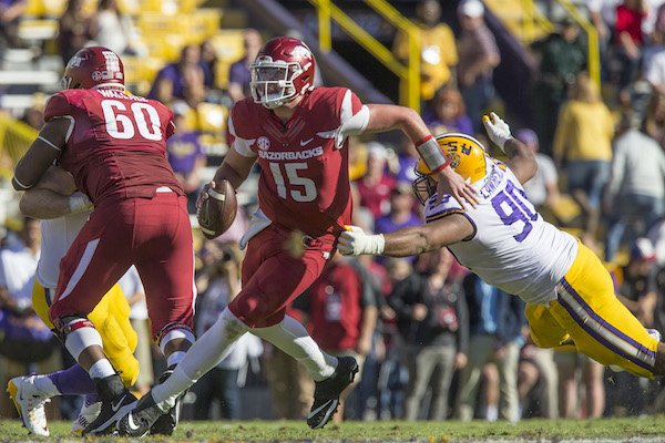 Cole Kelley (15), Arkansas quarterback, evades Rashard Lawrence, LSU defensive end, in the fourth quarter Saturday, Nov. 11, 2017 at Tiger Stadium in Baton Rouge, La.