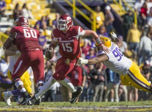 NWA Democrat-Gazette/Ben Goff NO ESCAPE: Redshirt freshman Arkansas quarterback Cole Kelley (15) evades LSU defensive end Rashard Lawrence in the fourth quarter Saturday at Tiger Stadium in Baton Rouge, La. Kelley, who was arrested Sunday morning on suspicion of driving while intoxicated and reckless driving, has been indefinitely suspended from the team by head coach Bret Bielema.