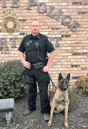 Submitted Photo Officer Bryan Smith has recently been promoted to corporal, according to a report by Gravette police chief Chuck Skaggs at the Nov. 9 committee of the whole meeting. Smith has been with the Gravette Police Department five years and has been a canine handler the last 18 months. He is pictured here with K-9 IKKS, the department's canine officer. Smith and K-9 IKKS were recently successful in locating a missing six-year-old with disabilities in the Highfill area. They tracked the boy into the woods and located him unharmed.
