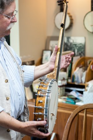 NWA Democrat-Gazette/LARA JO HIGHTOWER Clark Buehling, shown here in his music studio, has a large collection of banjos, his favorite stringed instrument. His passion is 19th-century banjo, mandolin and fiddle music.