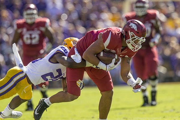 Arkansas tight end Jeremy Patton tries to break the tackle of LSU defender John Battle during a game Saturday, Nov. 11, 2017, in Baton Rouge, La.